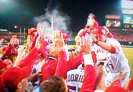 DCP02591.JPG: Erstad gets high-fives from his teammates after a solo home run bringing the Angels to within one.